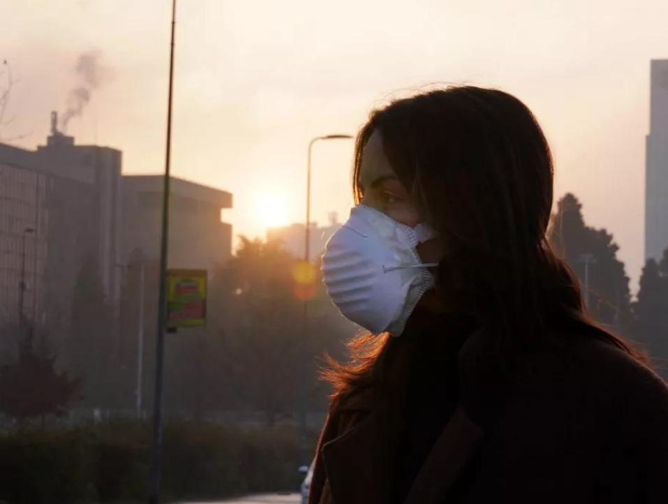 una persona in città indossa una mascherina e pensa al cambiamento